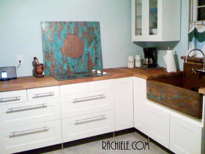 kitchen with copper farmhouse sink and copper cooktop backsplash