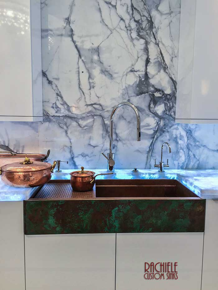 copper farmhouse sink with marble walls