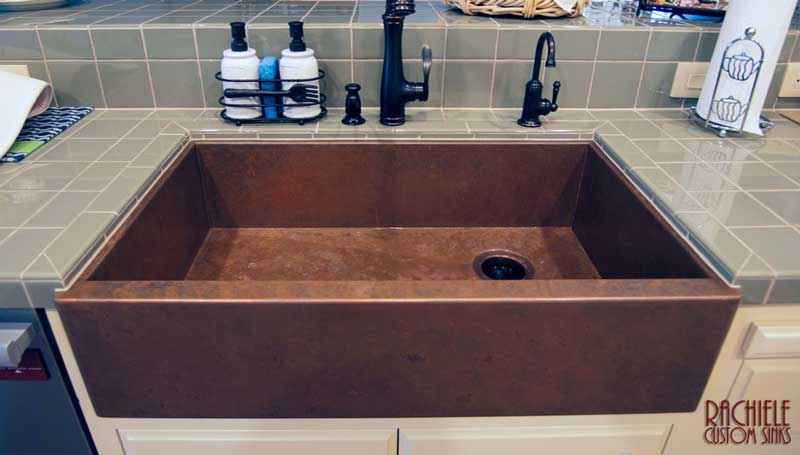 copper farm sink under blue-green tile