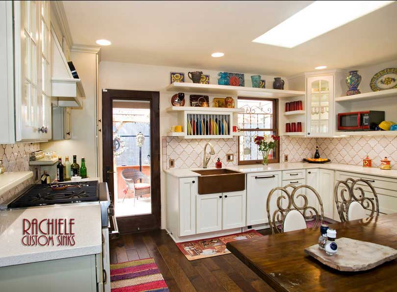 Copper apron farmhouse sink in country kitchen with white cabinetry