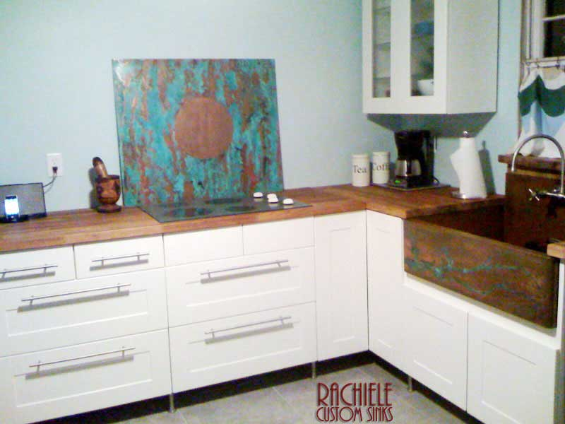 custom copper farmhouse sink and wall behind cooktop